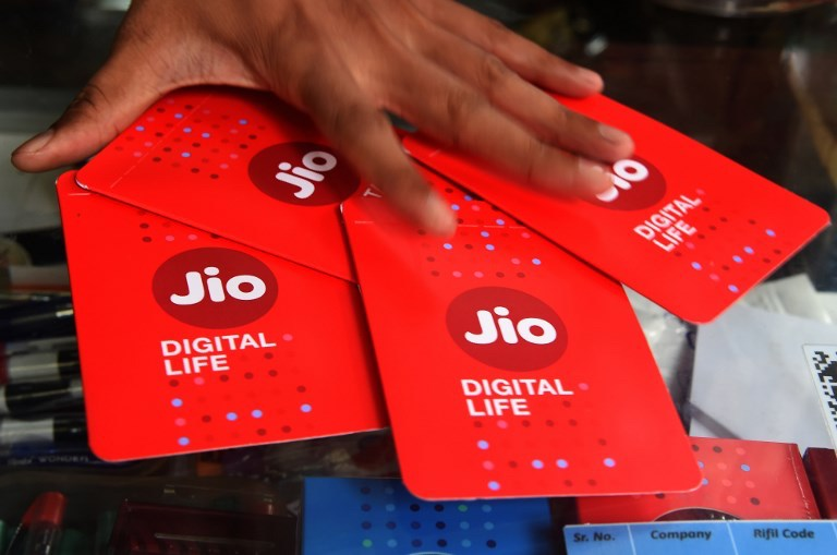 A shopkeeper collects Jio SIM cards at a mobile-phone store in Mumbai. Photo: AFP / Indranil Mukherjee