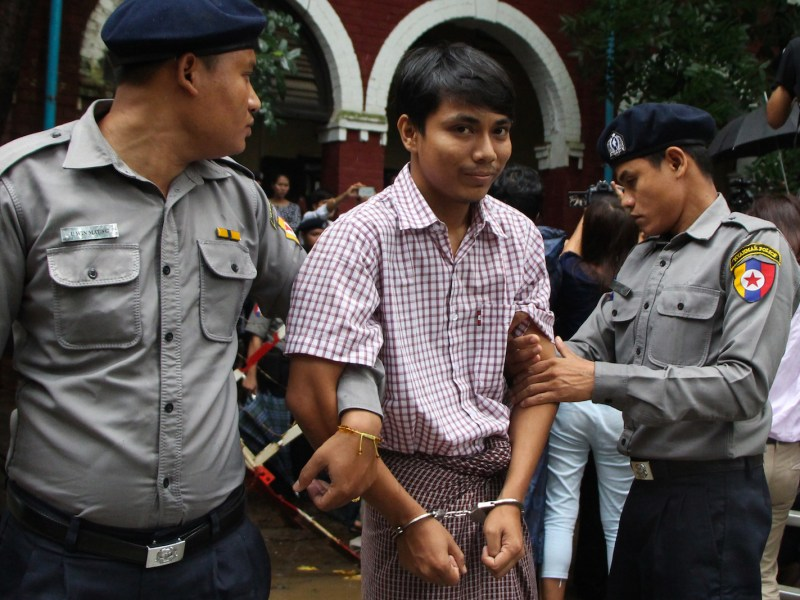 Detained Myanmar journalist Kyaw Soe Oo (C) is escorted by police to a court for his ongoing pre-trial hearing in Yangon, July 9, 2018. Photo: AFP/Stringer