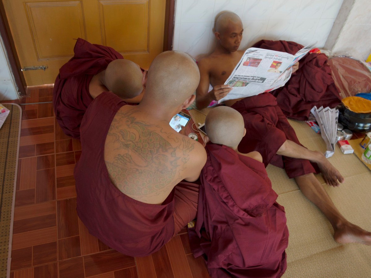 A Myanmar monk checks his Facebook with two Buddhist monk novices, April 11, 2016. Photo: AFP/Romeo Gacad