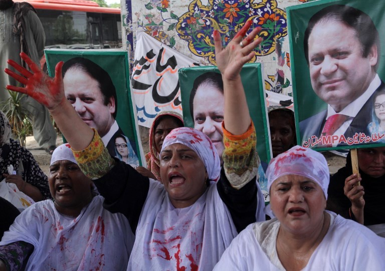 Shroud-wearing activists of the Pakistan Muslim League-Nawaz party shout slogans as they take part in a protest in Multan on July 8, 2018, after a sentencing decision against former prime minister Nawaz Sharif. Photo: AFP / SS Mirza