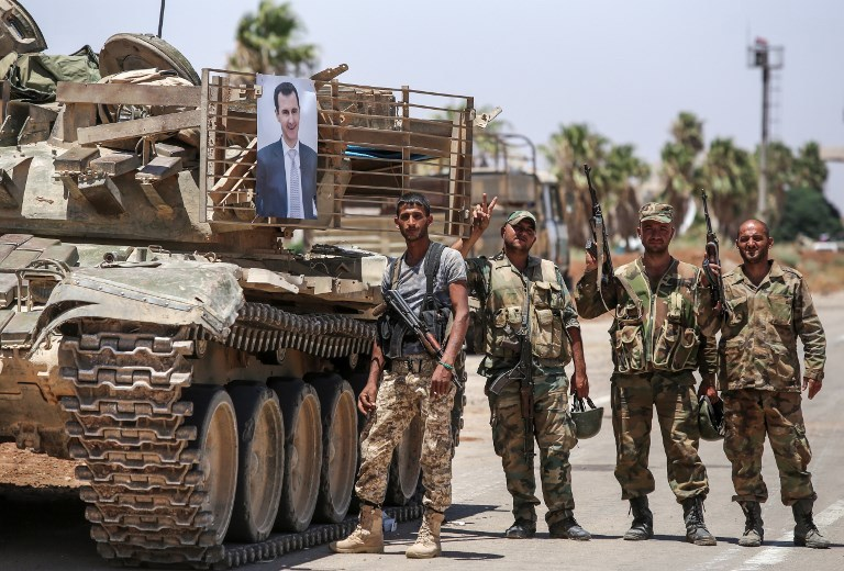 Syrian government soldiers stand flashing the victory gesture next to a picture of Syrian President Bashar al-Assad hanging on a tank at the Nassib border crossing with Jordan in the southern province of Daraa on July 7, 2018. Photo: AFP / Youssef Karwashan