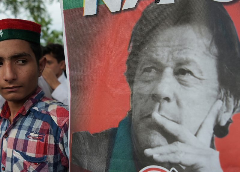 PTI黨主席伊姆蘭汗的支持者站在這位成為政治家的前板球明星一張海報旁邊。相片:AFP / Aamir Qureshi