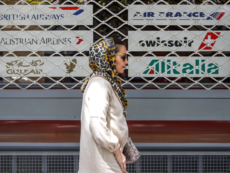 An Iranian woman walks past the shuttered window of the closed offices of a travel agency showing the logos of various air lines in the capital Tehran.  AFP / STRINGER