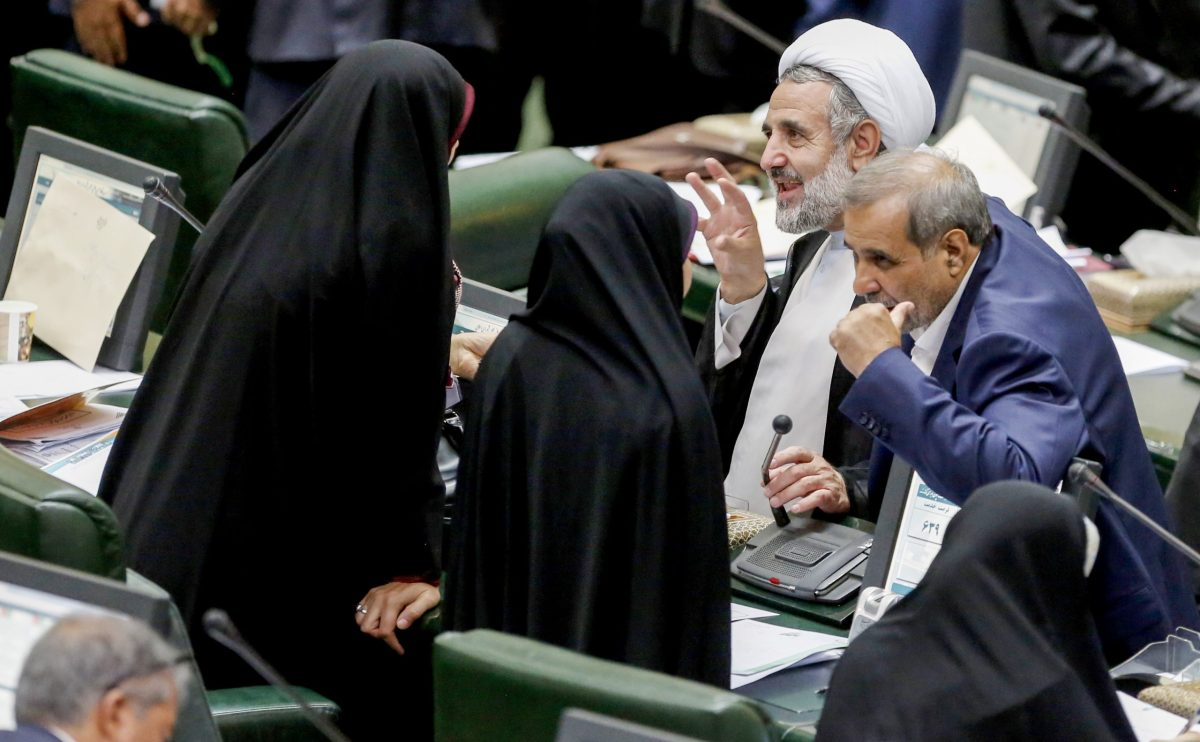 Iranian MPs engage in discussions while the economy minister speaks during a parliamentary session in Tehran on August 26, 2018, before a vote that saw Masoud Karbasian impeached. Photo: AFP / Atta Kenare