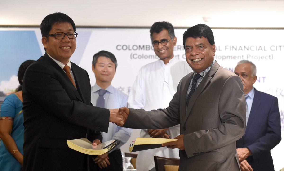 Sri Lankan Megapolis and Western Province Development Ministry secretary Nihal Rupasinghe (2R) and China Harbour engineering company director Tang Qiaoliang (L) shake hands as  Megapolis and Western Province Development Minister Patali Champika Ranawaka (C) looks on during an agreement signing ceremony in Colombo on August 12, 2016.  / AFP PHOTO / ISHARA S.KODIKARA