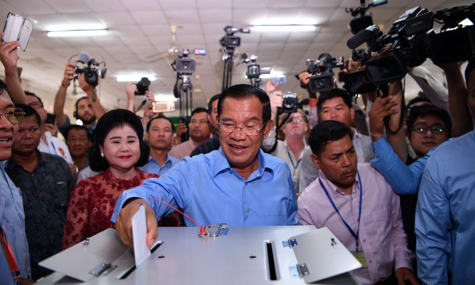2018年7月29日,柬埔寨總理洪森(圖中)在大選期間於金邊投票,他的妻子文拉妮(Bun Rany)(左中)在旁觀察。照片:AFP / Manan Vatsyayana
