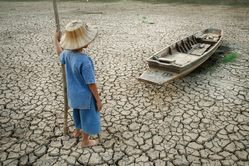 Children standing near the wooden boat on cracked earth. Metaphor for Global warming and Climate change. Photo: iStock