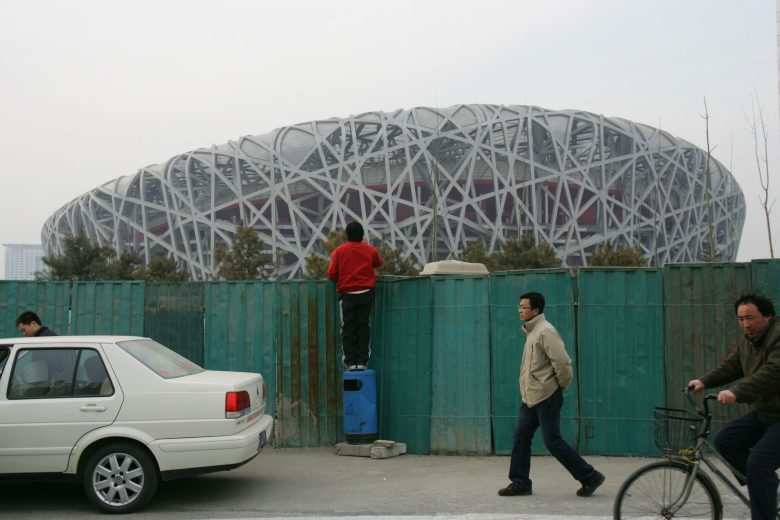 A file photo shows a migrant worker standing on the top of a litter bin to have a look at the National Stadium. Photo: WeChat via dixphoto