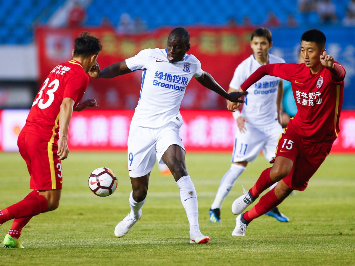 Shanghai Greenland Shenhua's Demba Ba, center, wriggles pass two Changchun Yatai players. Photo: AFP