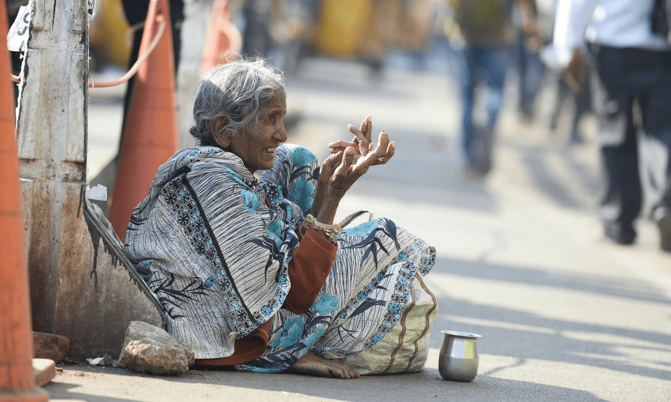 A woman begs on the side of a road in Hyderabad city. AFP
