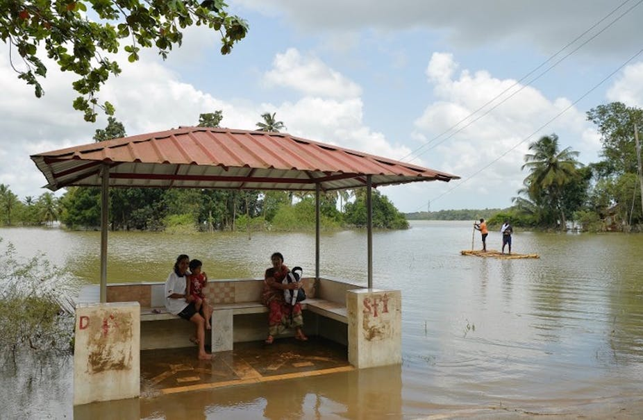 Residents of Pandanad sit in a bus stop surrounded by flood waters in Kerala. Photo: AFP/Manjunath Kiran