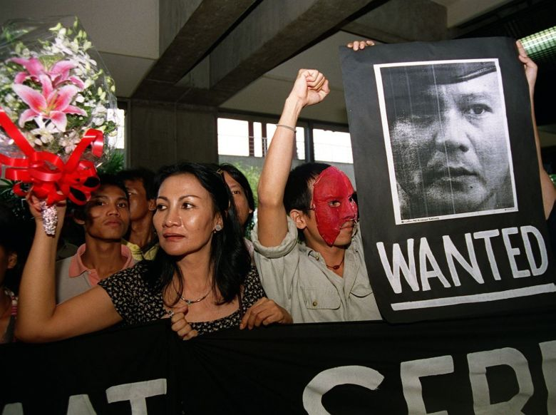 Indonesian Pro-reform activists, some in masks resembling those worn by their kidnappers, gather at Jakarta's international airport 19 July with a wanted sign for General Prabowo Subianto, the former commander of the special forces and a son-in-law of ex-president Suharto. The activists were welcoming back kidnap victim Pius Lustrilanang from the Netherlands where he fled in fear of his life after exposing security  forces involvement in the abduction of 23 activists, 14 of whom are still missing.  Prabowo has said he will accept responsibility for the abductions.    AFP PHOTO. Dadang Tri.    . / AFP PHOTO / DADANG TRI