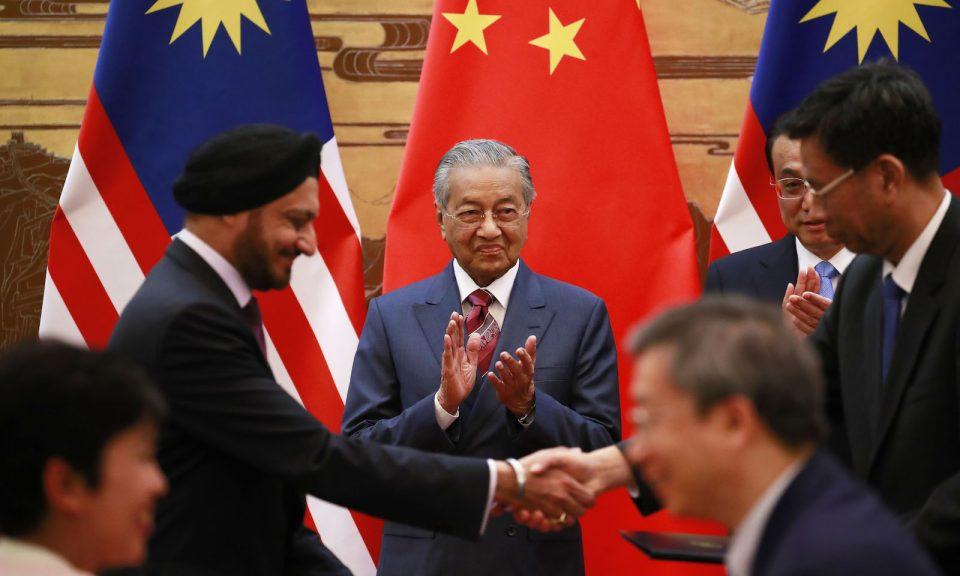 2018年8月20日,在北京人民大會堂舉行的簽字儀式上,馬來西亞總理馬哈蒂爾(中)和中國總理李克強(左二)在雙方代表交換文件時拍手。相片:AFP / Pool / How Wee Young