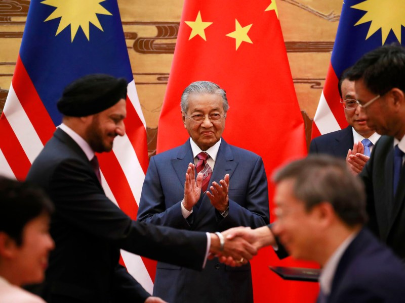 Malaysia's Prime Minister Mahathir Mohamad (C) and China's Premier Li Keqiang (2nd R) clap as delegates exchange documents during a signing ceremony at the Great Hall of the People in Beijing on August 20, 2018. Photo: AFP/Pool/How Wee Young