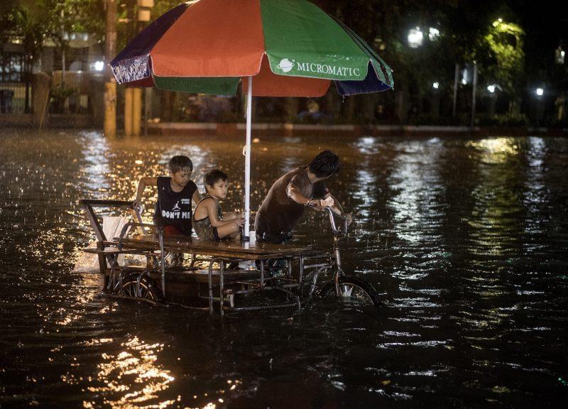 2018年8月11日,熱帶風暴摩羯引發傾盆大雨,一輛人力車司機和兒童在街道上被水淹沒。相片:AFP / Noel Celis