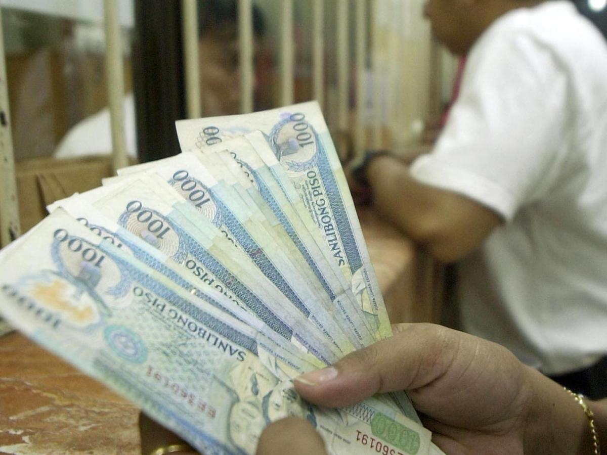 A customer counts 1,000 peso bills after converting her dollars at a money shop in the suburban financial district of Makati 24 August 2003 . The Philippine currency, languishing at levels last seen two and a half years ago, is expected to breach its historic low against the US dollar amid persistent political concerns, analysts say. The peso has been hitting records lows recently and is now hovering above the 55-to the dollar mark. AFP PHOTO Joel NITO / AFP PHOTO / JOEL NITO
