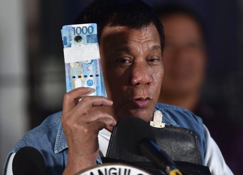 菲律賓總統杜特爾特於2017年6月20日拿著一疊比索鈔票。相片:AFP / Ted Aljibe