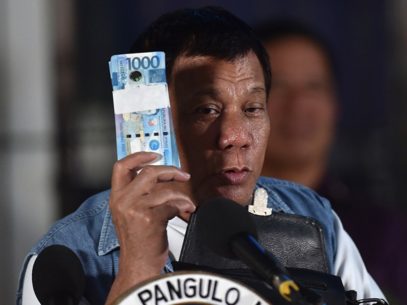 Philippine President Rodrigo Duterte holds a wad of peso bills on June 20, 2017. Photo: AFP/Ted Aljibe