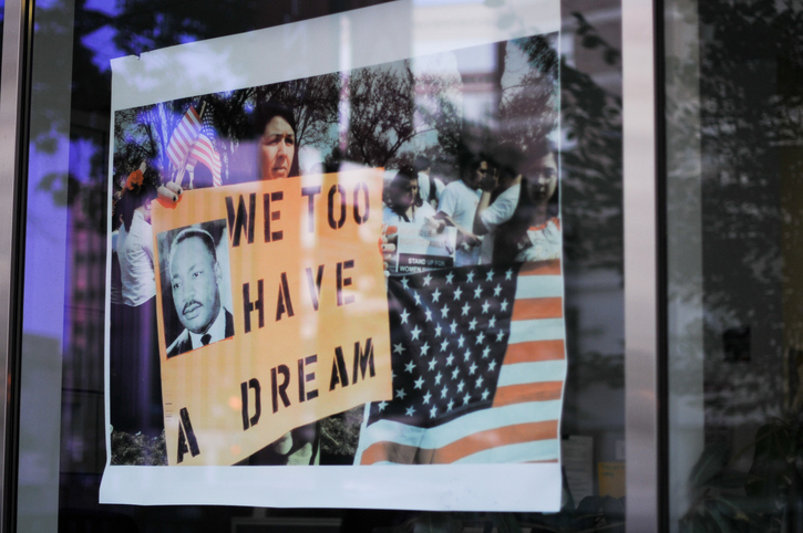 In Washington, DC, on July 8, 2011, demonstrators are reflected in a shop window shop, as a woman carries a placard with the image of Martin Luther King and the slogan 'We Too Have a Dream'. Photo: iStock