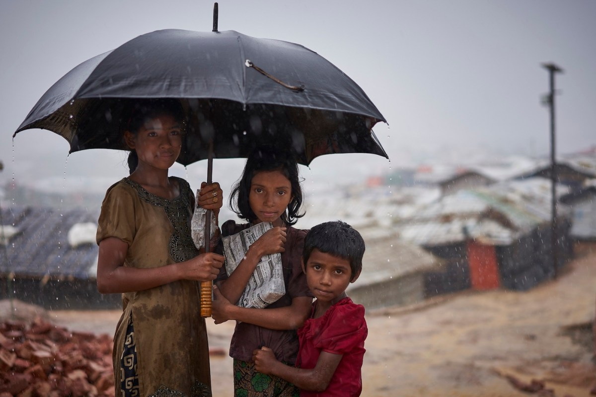 Rohingya refugees walk down a footpath during a heavy monsoon downpour in Kutupalong refugee camp in Cox's Bazar, southern Bangladesh. Photo: UNHCR
