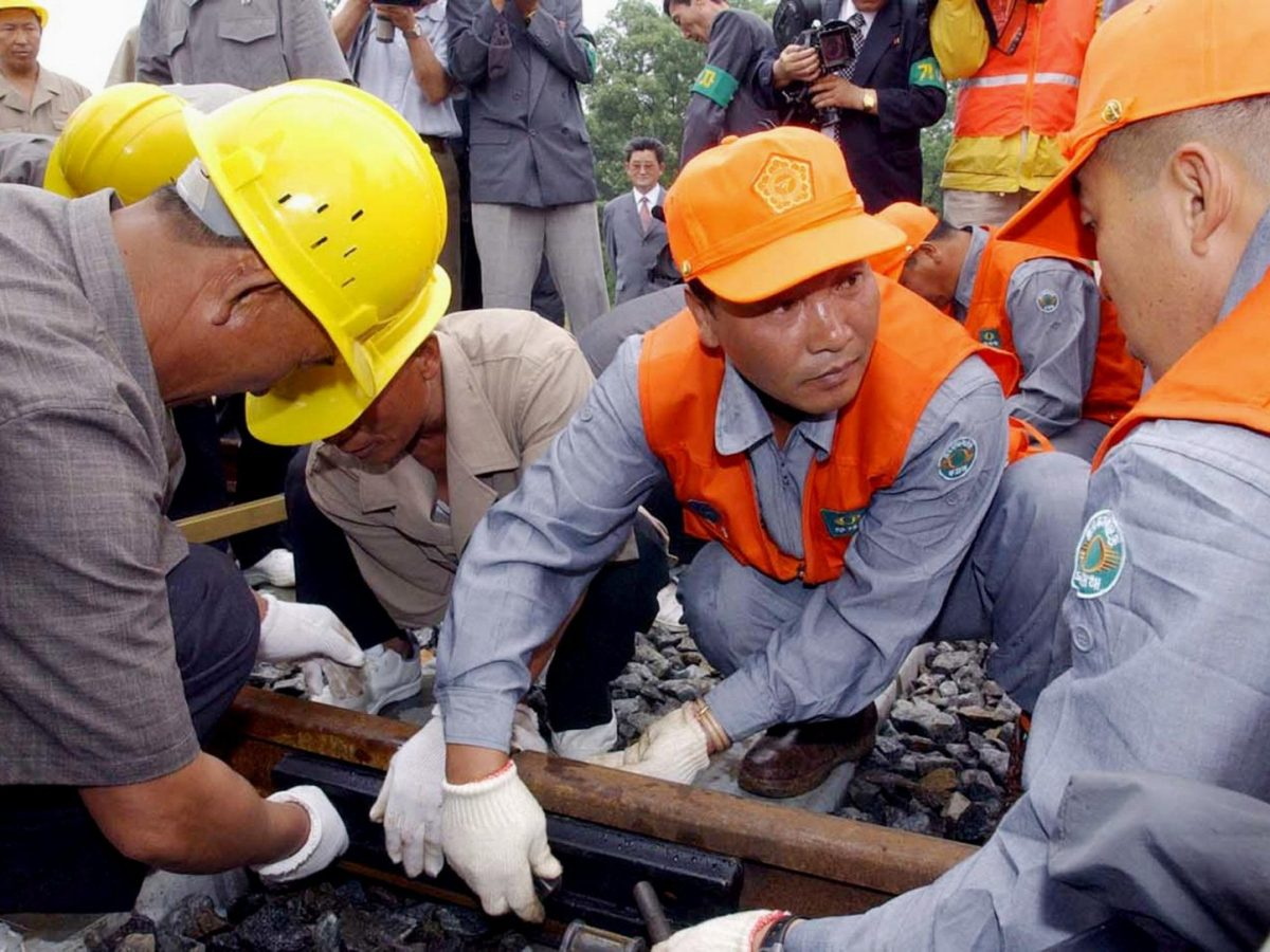 A South Korean worker in an orange cap with his North Korean counterpart in yellow connect a rail line during a symbolic ceremony to re-link their railways in the demilitarized zone on June 14, 2003. The South is trying to increase ties with the North. Photo: AFP/Photo pool