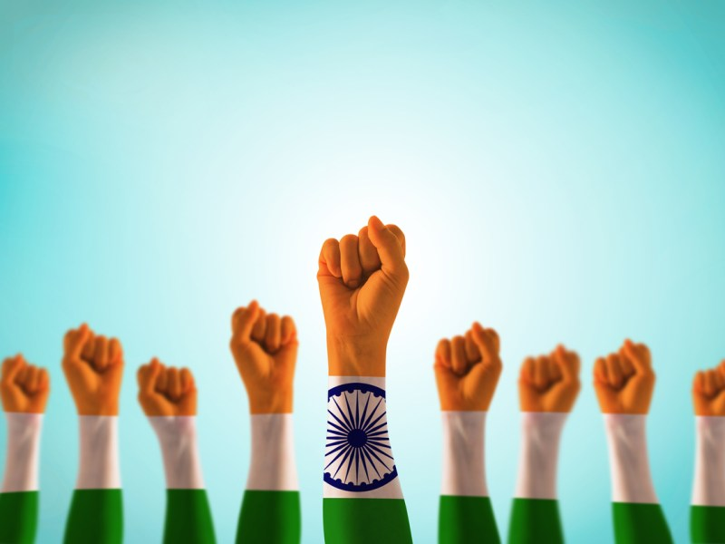 India national flag pattern on leader's fist isolated (clipping path) on blue mint sky for Human equal rights, labor day concept