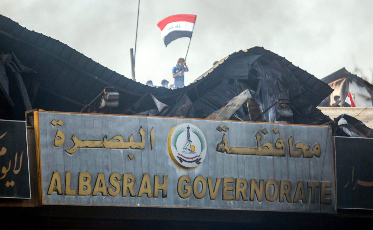 An Iraqi protester waves a national flag while demonstrating outside the burnt-down local government headquarters in the southern city of Basra on September 7. Photo: AFP / Haidar Mohammed Ali