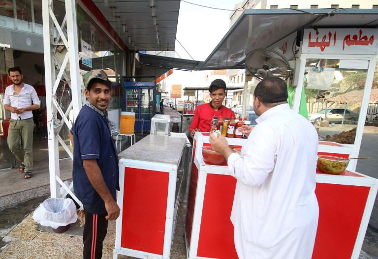 Iraqis buy food from a vendor in the southern Iraqi city of Basra on September 9. Photo: AFP