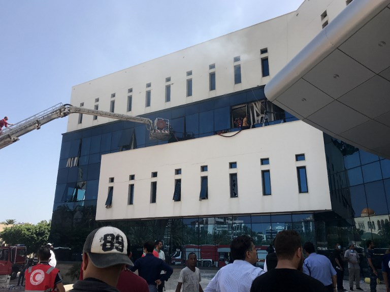 Firefighters and onlookers gather in front of the headquarters of Libya's National Oil Company in the capital Tripoli on September 10, after amed men stormed the building.  Photo: AFP