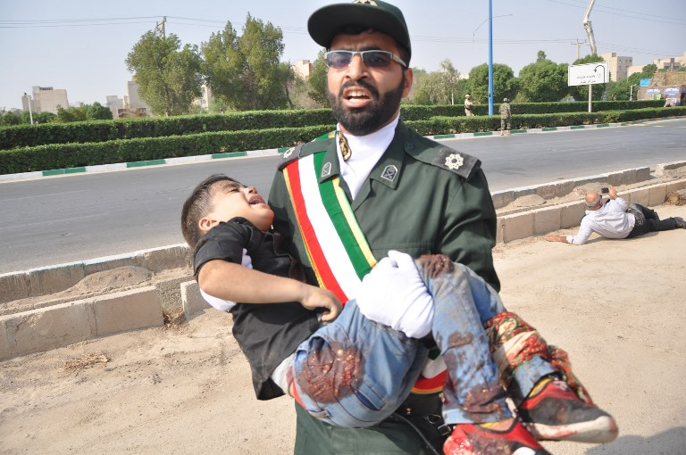 A member of Iran's Revolutionary Guards Corps carries an injured child at the scene of an attack on Saturday on a military parade  in the southwestern Iranian city of Ahvaz. Photo: AFP