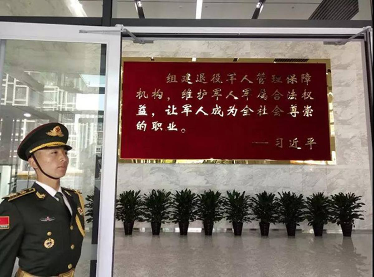 A PLA soldier stands guard at the Ministry of Veteran Affairs. A plaque of Xi Jinping's notice to take good care of veterans is seen in the background. Photo: Xinhua