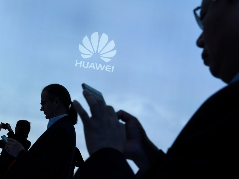 Visitors use their mobile phone at a Huawei promotional stand. Photo: AFP