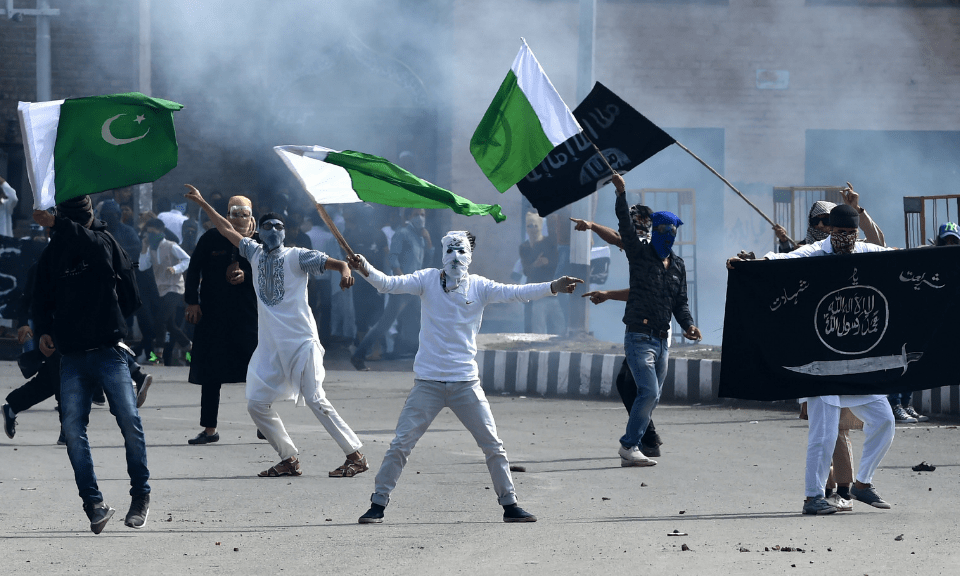 Kashmiri youths wave the flags of Pakistan and Islamic State (ISIS) during clashes between protesters and Indian government forces in Srinagar. Photo: AFP