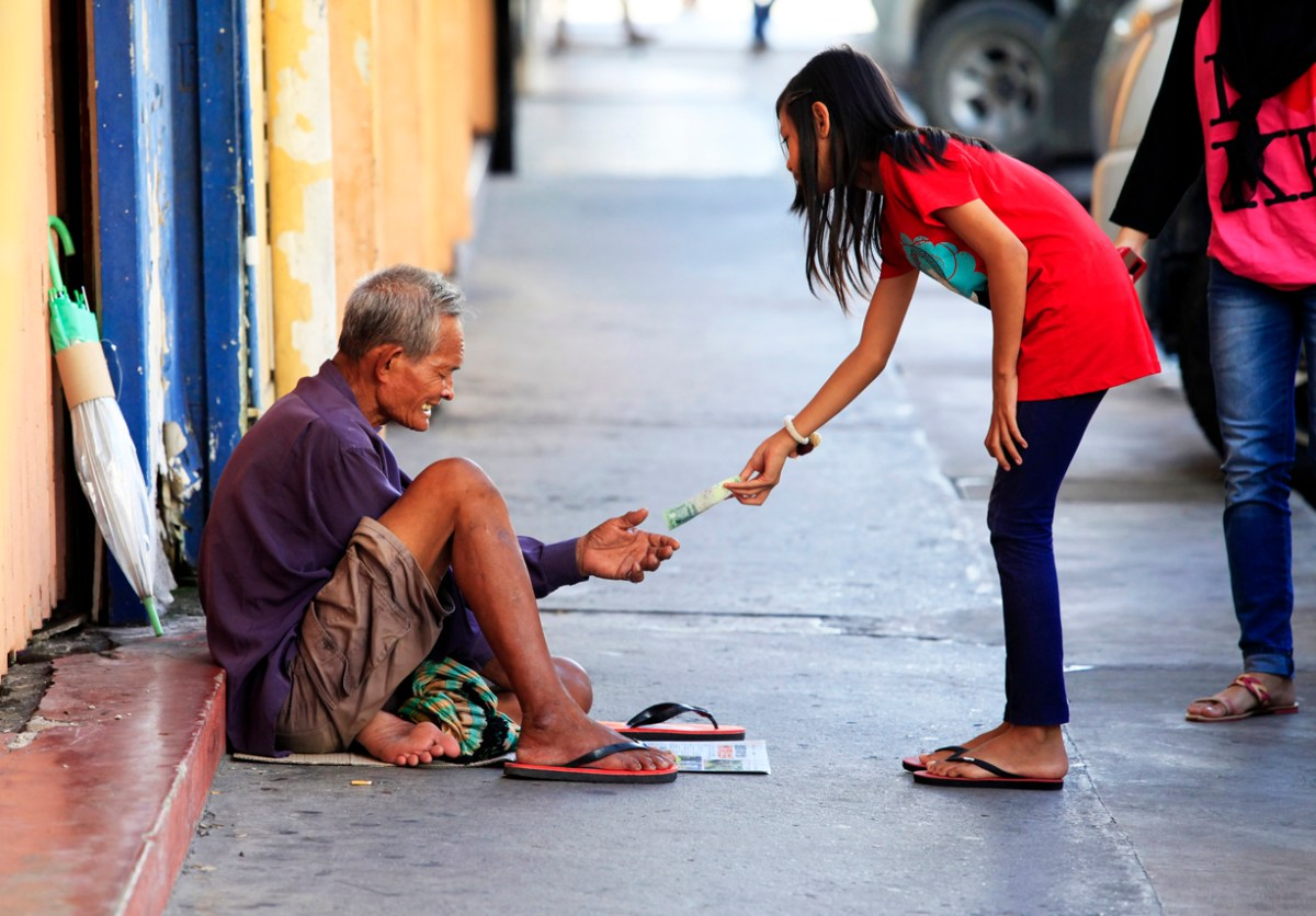 Kota Kinabalu, Malaysia - January 3, 2015: Young girl gives money to a beggar on a street in Kota Kinabalu. Photo: iStock