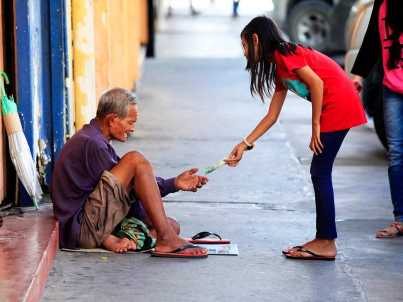Kota Kinabalu, Malaysia - January 3, 2015: Young girl gives money to a beggar on a street in Kota Kinabalu. Photo: iStock