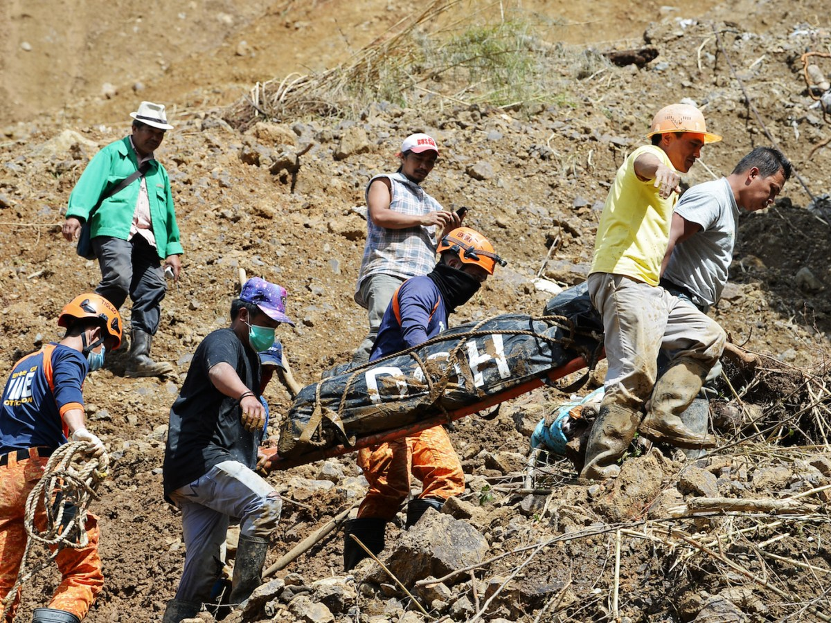 Rescuers carry a body bag containing a landslide victim triggered by heavy rains during Typhoon Mangkhut, in Itogon, Benguet province on September 18, 2018. Photo: AFP/Ted Aljibe