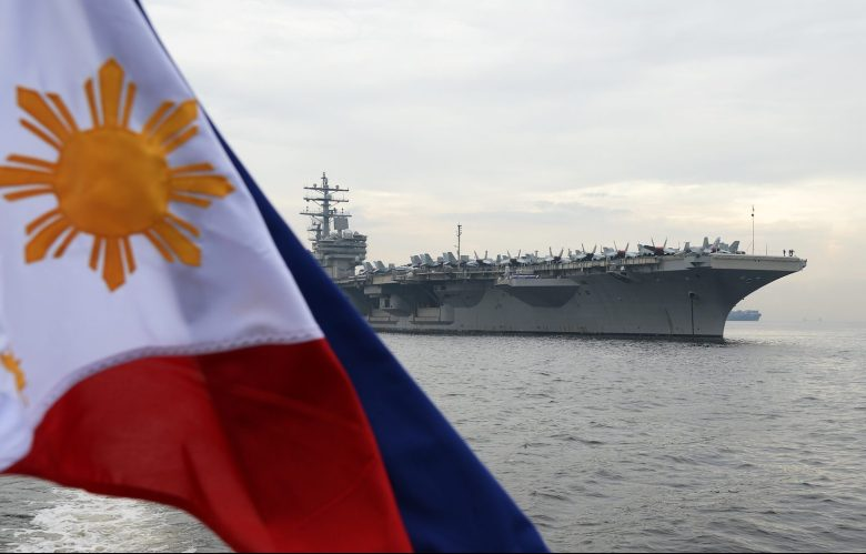 A Philippine flag flutters as the nuclear-powered aircraft carrier USS Ronald Reagan (CVN-76) anchors off Manila Bay, June 26, 2018. Photo: AFP/ Ted Aljibe