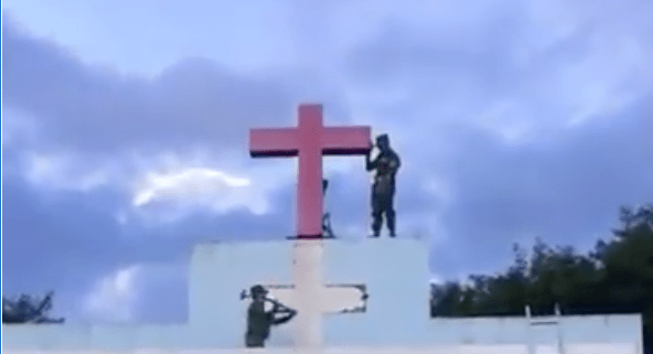 Soldiers thought to be from the United Wa State Army take down a cross from a building in the Wa region in northern Shan State. The soldier below uses a sledgehammer to demolish the top of the building, believed to be an unauthorized church. Photo: Screen grab from video.