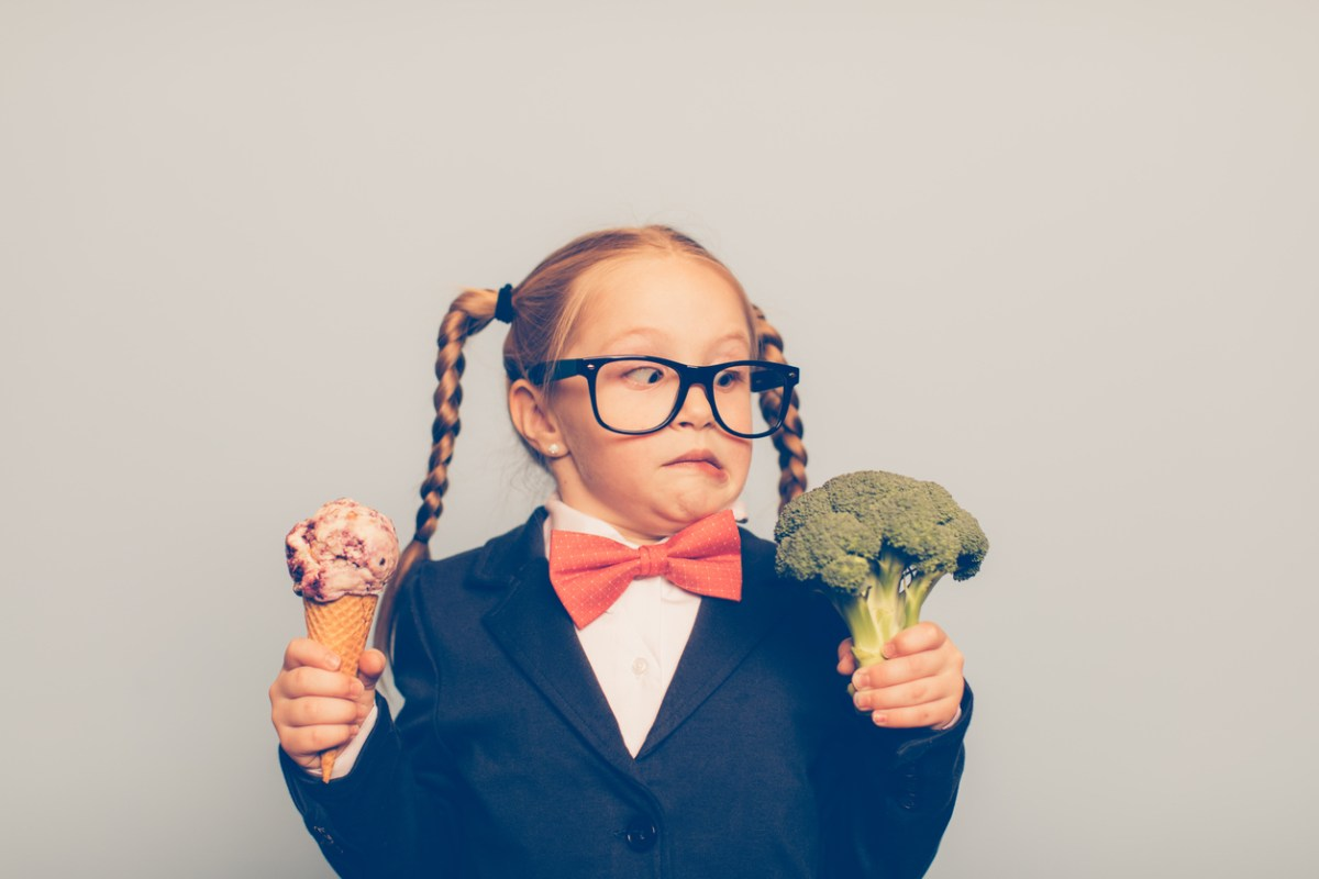 A young female nerd dressed in bow tie and eyeglasses is deciding between eating an ice cream cone or broccoli. She is making a disgusted face at the broccoli. She is choosing the treat. Photo: iStock