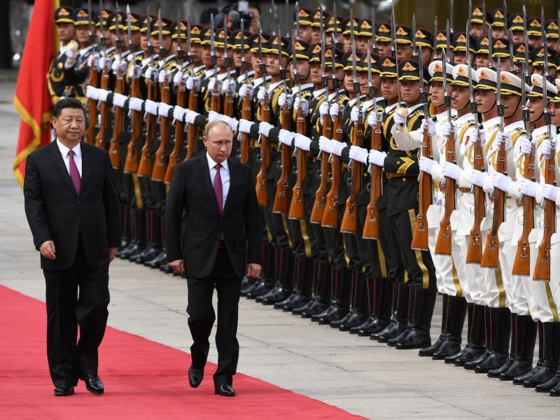 Russia's President Vladimir Putin (center) reviews a military honor guard with Chinese President Xi Jinping (left) outside the Great Hall of the People in Beijing on June 8, 2018. Photo: AFP / Greg Baker