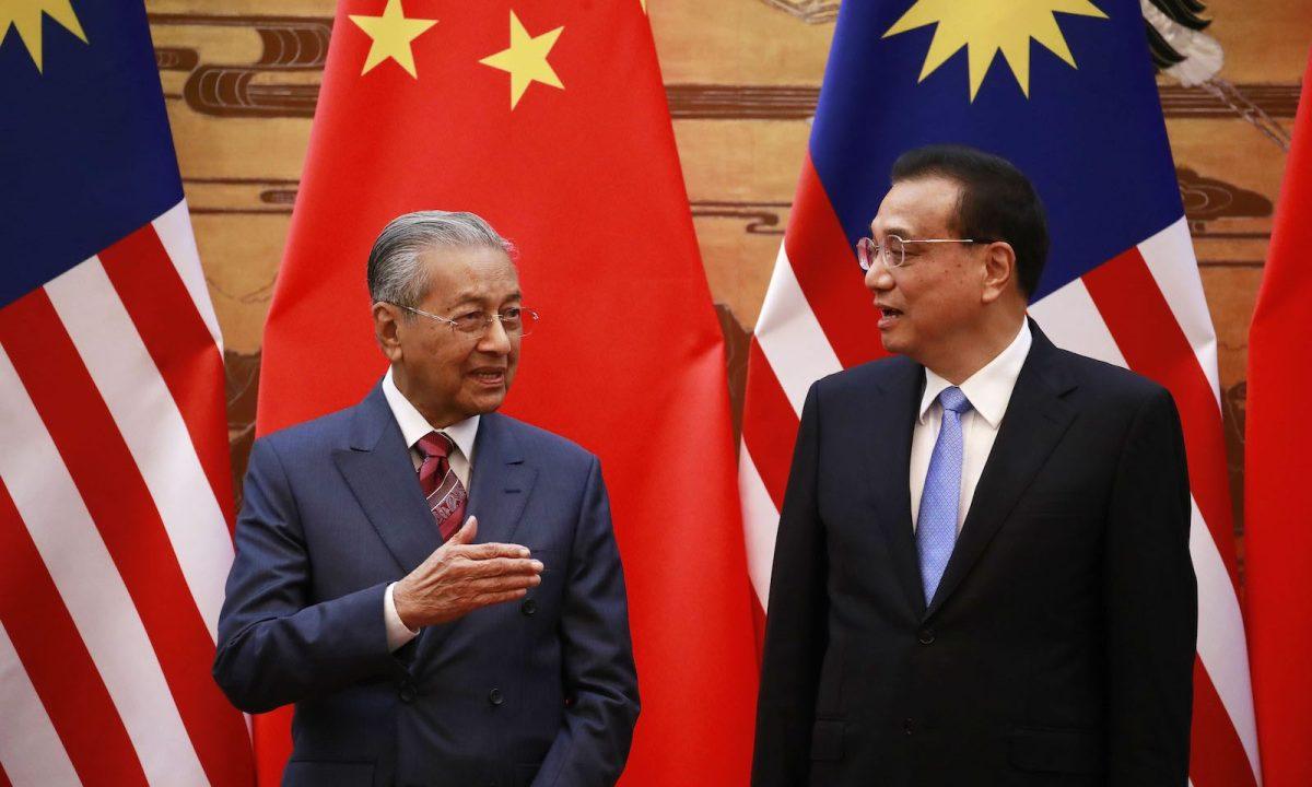 馬來西亞總理馬哈蒂爾(左)和中國總理李克強於2018年8月20日在北京人民大會堂舉行簽字儀式時交談。相片: AFP / POOL / How Hwee Young