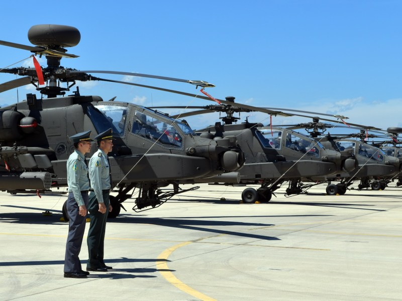 Two Taiwan servicemen stand in front of US-made Apache AH-64E attack helicopters during a commissioning ceremony at an military base in Taoyuan on July 17, 2018. Photo: AFP / Sam Yeh