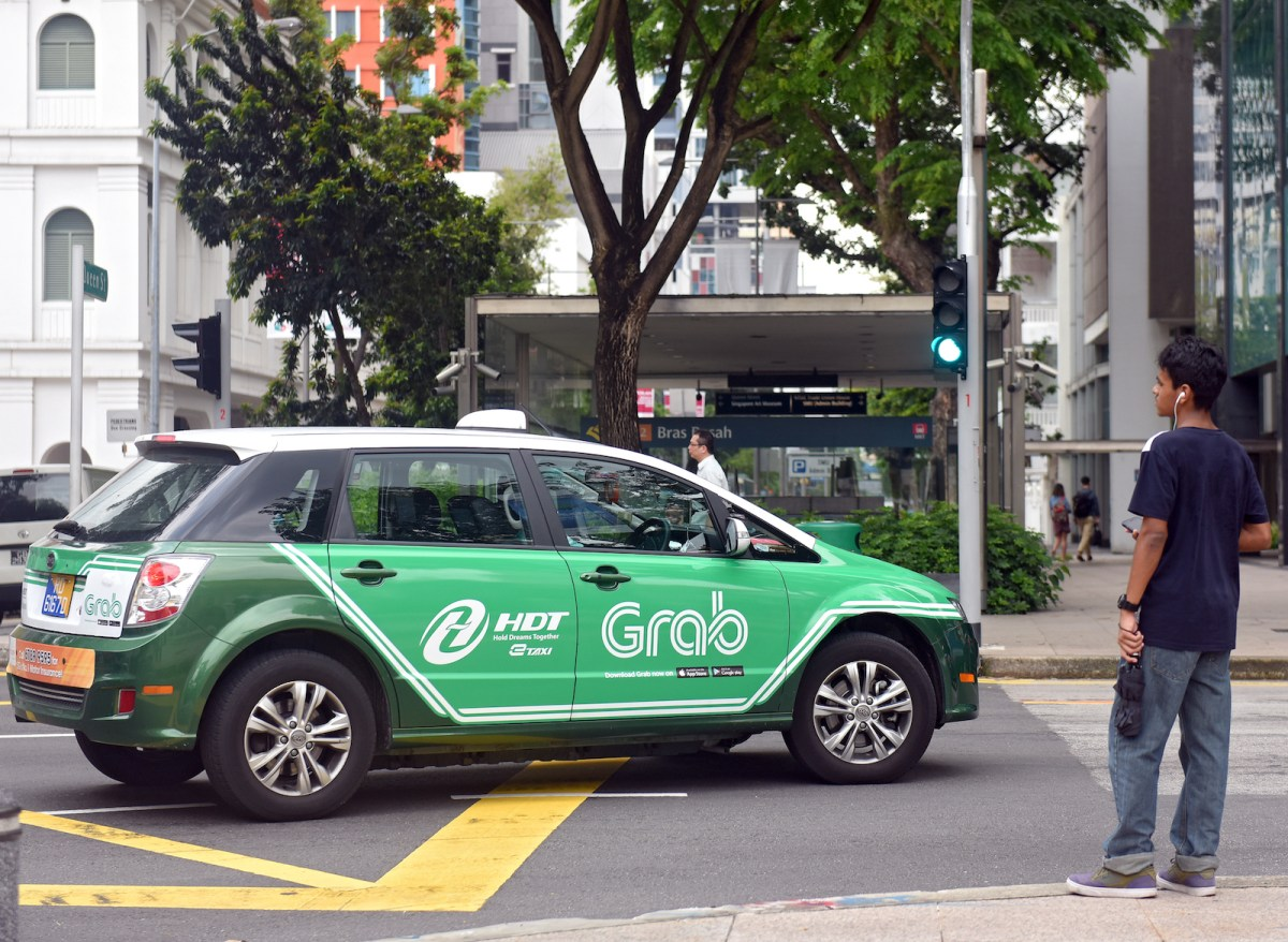 A taxi with the Grab advertisement in Singapore. The company is finding it more difficult to do business in Thailand. Photo: AFP