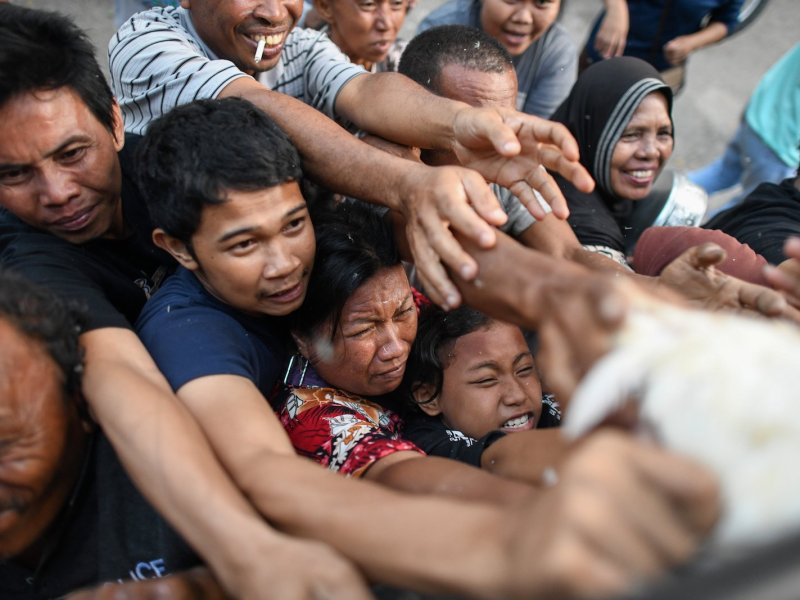 Earthquake survivors scuffle to get live chickens being distributed from a police truck outside a makeshift camp in Palu.  Photo: AFP / Jewel Samad