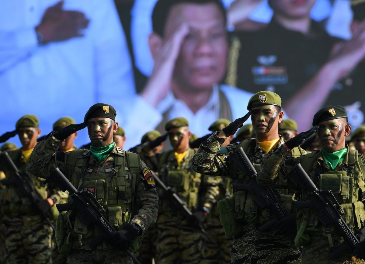 Philippine President Rodrigo Duterte (in video screen) salutes along with soldiers during the 121st founding anniversary of Philippine army at the army headquarters in Manila on March 20, 2018. Photo: AFP/Ted Aljibe