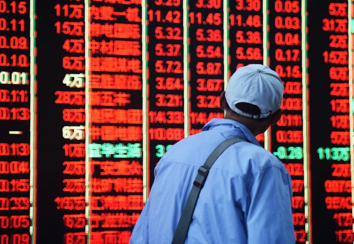 A Chinese investor walks past a screen displaying stocks rising (red is up and green is down) across the board in Shanghai. Photo: AFP