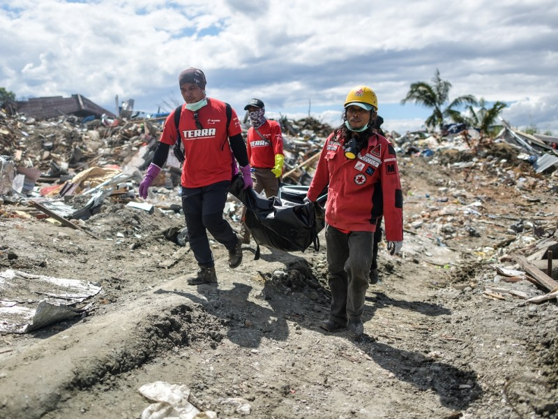 Indonesian rescuers carry a dead body from the debris in Petobo in Sulawesi on Sunday, following the Sept 28 earthquake and tsunami. Nearly 2000 bodies have been recovered from Palu but thousands are still missing. Photo: AFP / Mohd Rasfan