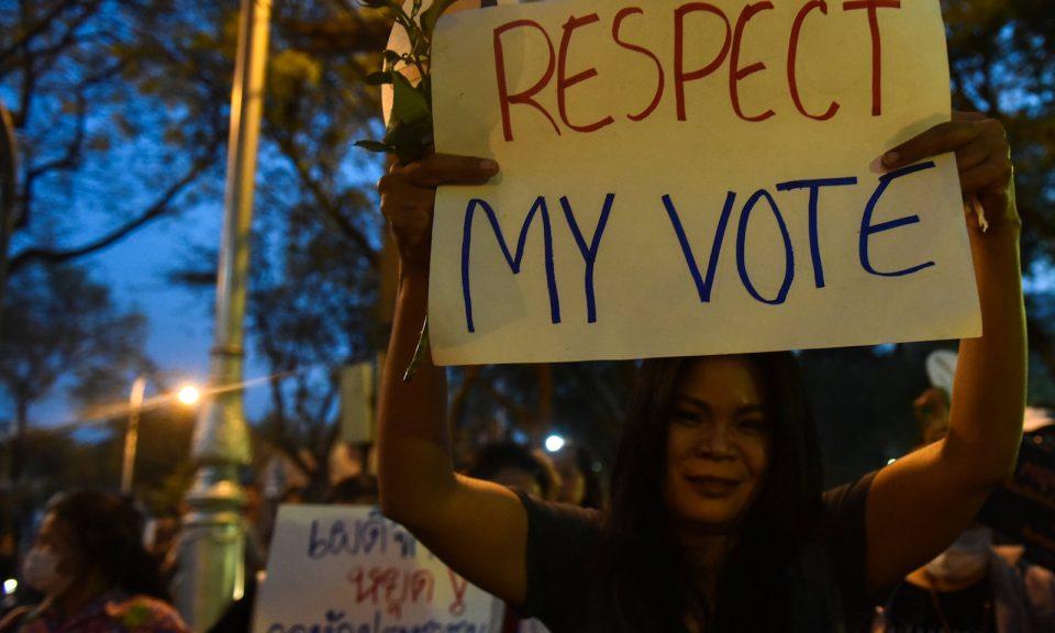 2018年3月24日,一名高舉標語牌的示威人士與其他示威者在泰國曼谷的軍隊總部附近抗議軍政府 。相片:Reuters / Panumas Sanguanwong