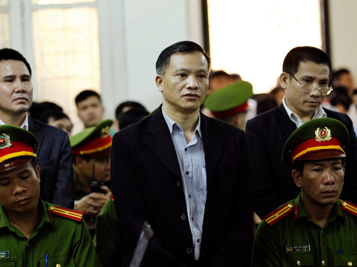 """Nguyen Van Dai (C) and other political activists Pham Troi (L) and Naguyen Trung Ton (R) stand in a courtroom during their trial in Hanoi on April 5, 2018.Several protesters were hauled off by plainclothes police in Hanoi on April 5 as they marched to the trial of high-profile lawyer Nguyen Van Dai and five others charged with """"attempting to overthrow the state"""". / AFP PHOTO / Vietnam News Agency / Vietnam News Agency"""