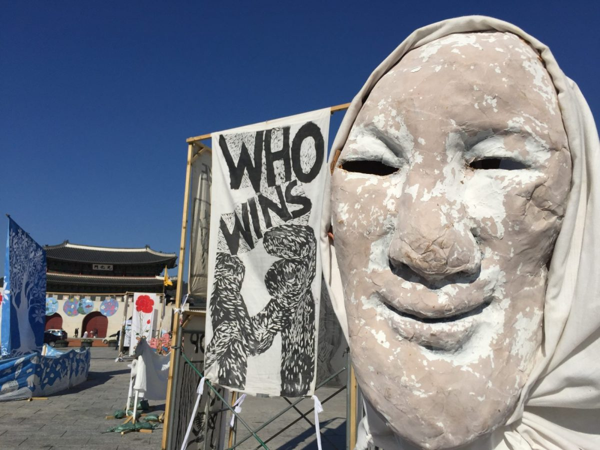 Who wins? A ghostly face, styled after a traditional Korean mask, asks a perennial question about war. White is the Korean color of death. In the background sits the gate of Gyeongbok Palace - the building around which the capital was built exactly 100 years before Columbus landed in America. Photo: Andrew Salmon/Asia Times